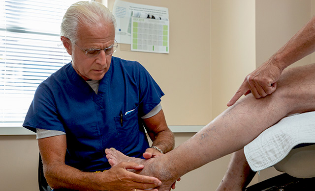 Dr. Elias examining the ankle of a patient