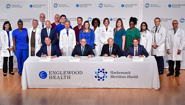 Warren Geller, president and CEO, Englewood Health; Thomas C. Senter, Esq., chairman, Board of Trustees, Englewood Health; Gordon N. Litwin, Esq., chairman, Board of Trustees, Hackensack Meridian Health; and Robert C. Garrett, FACHE, CEO, Hackensack Meridian Health. The two health care systems have signed a definitive agreement to merge. Also pictured are physicians, nurses, and other clinical staff from Englewood Health and Hackensack Meridian Health.